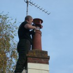 Fitting a bird guard to a chimney pot.